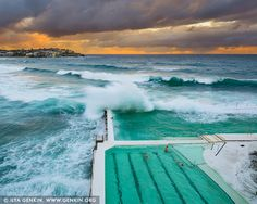 Waves Crushing at Bondi Icebergs, Bondi Beach, Sydney, NSW, Australia. Huge waves crashing over the swimming pools at the Bondi Icebergs Club on a beautiful morning in Sydney, NSW, Australia. Sydney's most famous beach is Bondi. At its southern end is Bondi Baths or Bondi Icebergs swimming pool, an eight-lane, 50-meter saltwater pool built into the cliffs. Open every day except Thursdays, it is home to the Bondi Icebergs Club, which was founded in 1929 by a small group of friends. To become…