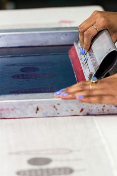 Silk screen printing onto fabric using emulsion to create a permanent stencil.