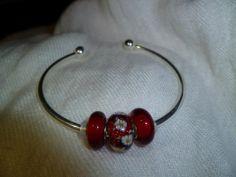 Bracelet Style Bangle plaqué en Argent avec les charme (perle style Pandora) que vous voulez.
