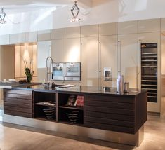 Beautiful kitchen design where the island appears to be floating against a neutral, light, background. Multiform showroom.