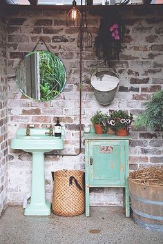 Beautifully weathered brick, a terrazzo floor, and vintage sink. This bathroom has personality.baby space interiors