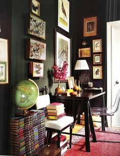 Dark walls, trestle-base desk and Lucite chair by IKEA, butterfly collection found at a Paris flea market, and a vintage globe displayed on a set of Encyclopedia Britannica's Great Books of the Western World; the walls are painted in Benjamin Moore's Soot.  Apartment of Elaine Griffin and husband Michael McGarry in an 1890s Harlem brownstone.  Interior design by Elaine Griffin.  Photography by Joshua McHugh - Elle Decor