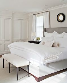 light grey & white. cabinetry and moldings.. circular mirror above headboard. Neat & Sheek.