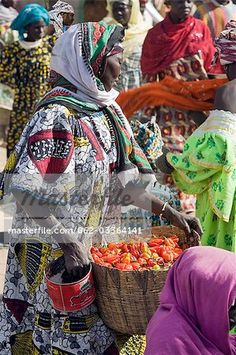Mali,Djenne. A woman carries a basket of red chillies at Djenne market. The weekly Monday market is thronged by thousands of people and is one of the most colourful in West Africa.