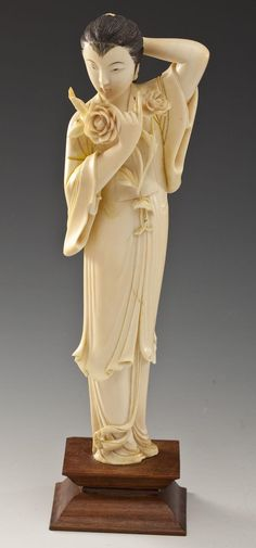 """DESCRIPTION: Carved ivory figure of a woman holding roses. Figure on wooden base. MEASUREMENTS: 12-1/4"""" tall with base. CONDITION: Base glued at center. Apparent toning consistent with age. Minor loss at right sleeve near elbow. Figure loosely attached to base. Evidence of paint on roses. IMPORTANT NOTE: Pre-ban and African in origin. Cannot be shipped out of the United States or to California, New Jersey, or New York. See Auction Terms & Conditions."""