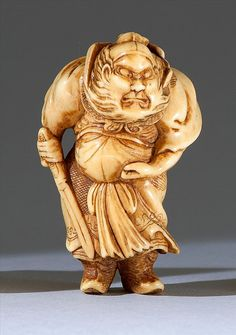 """IVORY NETSUKE In the form of Shoki standing with a drawn sword and a fierce expression on his face. Height 2.1"""" (5.3 cm)."""
