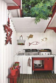 Cuisine d'extérieur rouge et blanche pour cette terrasse en bois. Plus de photos sur Côté Maison. http://petitlien.fr/7fce