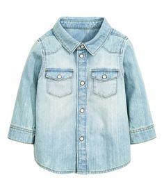 Azul denim pálido. Camisa en tejido denim suave y lavado con botones de presión anacarados. Modelo con bolsillos superiores con solapa y botón. Bajo