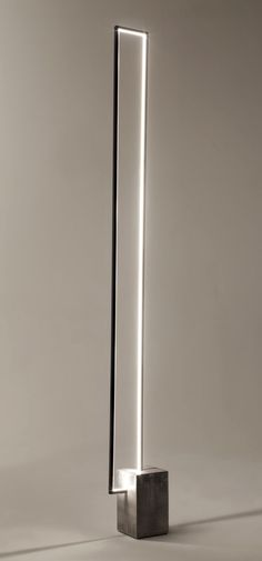The Mire : a floor lamp with a clear LED light strip inside a rectangular metal…