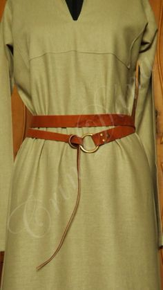 Cinto inspirado nos cintos longos utilizados pelor vários povos da Antiguidade e Medievo Europeus, em couro marrom envelhecido, com ponta fina e metal dourado envelhecido.