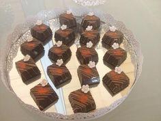 Caixinha em chocolate nobre recheada com ganache de laranja decorado com chocolate, flor, pérola e glitter comestível. Sabores e cores podem ser alterados de acordo com a preferência do cliente.
