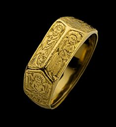 Gold ring, the broad hoop widening at the shoulders with foliate decoration merging with the double ridged bezel engraved with standing figures of two bearded saints, one holding a book. English, 15th century
