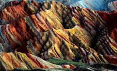 Zhangye Danxia Landform, Gansu Province, China. This naturally-formed landscape - a World Heritage site and a tourist attraction - astonishes visitors with the burst of colors with streaks of yellow, orange and red to emerald, green and blue that make it hard to believe it's real. The formation-process of this geo-park took over 24 million years in the Cretaceous age. If you plan on visiting, hope for the rain, as the vibrant hills glow even brighter after the rainfall - © 2013La boite verte
