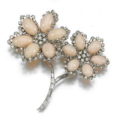 CORAL AND DIAMOND PARURE, 1960S.  Comprising: a brooch, pair of pendant earrings and a ring, set with cabochon coral and highlighted with baguette, brilliant- and single-cut diamonds, clip fittings. [Brooch only, see source for the rest of the parure.]