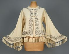 EMBROIDERED WOOL PAGODA SLEEVE JACKET, 1860s. Cream wool with elaborate silk frog closures decorated in grey and black silk tambour and satin stitch embroidery with silk tasseled fringe, silk lining. B-36, L-20 with 3 1/2 inch fringe. (Scattered small moth holes) good. $300-400