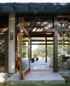 This impressive pivot glass door provides a welcoming entry to this modern abode in Hillsborough, CA. Paired against a wall of glass doors -- the natural light abounds. Houzz photo. Charlie Barnett Associates.