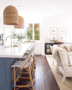 Gorgeous fall kitchen and living area. Love the rattan light pendants, blue kitchen island, Serena & Lily barstools, and the white granite counter tops. #kitchendesign #fallcolors