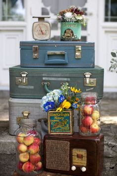 display of stacked vintage suitcases, mason jars filled with apples, old radio, tea tins