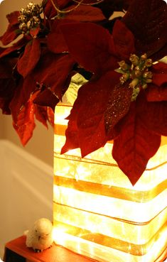 Lights in a glass vase, ribbon wrapped around it and poinsettias placed inside