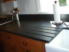 Black Cambrian granite in leather finish with integrated drainboard over apron sink