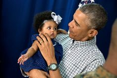President Barack Obama holds a young girl while meeting with Marine personnel and their families at Marine Corps Base Hawaii on Christmas Day, Dec. 25, 2014. (Official White House Photo by Pete Souza)