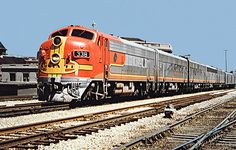 Santa Fe EMD F7A diesel electric locomotive # 338, leading four B-units, is in charge of a passenger train at the station in Joliet, Illinois, 06-25-1970