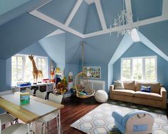 Blue playroom features a vaulted ceiling adorned with white beams placed above a nook filled with a beige sofa atop a blue geometric rug facing a Two's Company Hanging Rattan Chair.