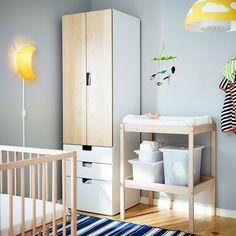 Una habitación de bebé con un cambiador y una cuna de haya y almacenaje en blanco/abedul