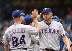 SEATTLE, WA - JULY 15:  Starting pitcher Matt Harrison #54 (R) of the Texas Rangers is congratulated by teammates after throwing a complete game shutout to defeat the Seattle Mariners 4-0 at Safeco Field on July 15, 2012 in Seattle, Washington.  (Photo by Otto Greule Jr/Getty Images)  game 89