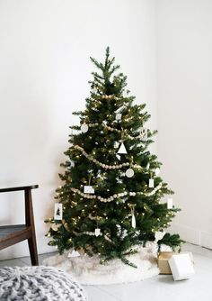 Christmas Tree Decoration Ideas - natural wooden ball garland + white geometric ornaments—a holiday tree for the minimalist.