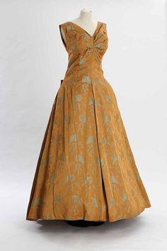 https://flic.kr/p/wDswKQ | Mustard evening dress | 1950s full length evening dress in antique gold coloured satin with figured blue shell design and with Oliver Messel's signature woven into the pattern. The dress is sleeveless with a V neck. It has a full length petticoat, a lightly boned taffeta bodice and stiffened fabric skirt. C2002.126 DPABRW42