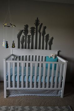 Painted Guitars behind Crib and DIY Guitar Mobile. OMG! If this doesn't scream Zeb & Amanda, I swear. Will be perfect for our little one! : )