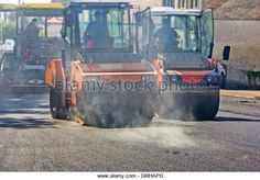 Roller compactor working on the new road construction site - Stock Image