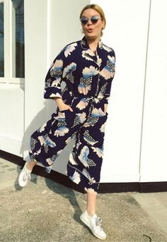 Lotte Williams wearing a Monki printed jumpsuit with white trainers and round sunglasses available at ASOS | ASOS Fashion & Beauty Feed