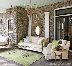 A sofa and club chair are upholstered in indoor-outdoor fabric on this covered porch. - Traditional Home ® / Photo: Werner Straube / Design: Linda Tallent Brown and Louise Kitchell