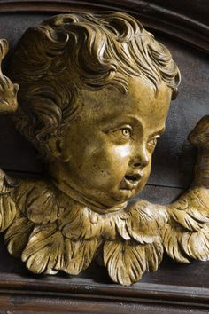 Close view of a carved wooden face of an angel on the seventeenth-century woodwork in the Chapel at Petworth House, West Sussex