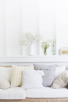 beach cottage summer room - pastel, white cushions, white flowers, wicker sofa, white panelling