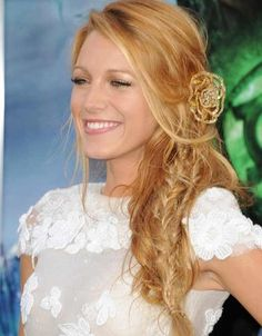 Long strawberry blonde with face framing highlights, a jeweled flower accessory, a side part and an over the shoulder messy fishtail braid hairstyle