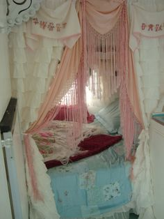 "Trailer decorated with vintage textile/linens giving the sleeping area a ""gypsy wagon"" look. ""Sweet and Dreams"" embroidered pillow cases hung above bed opening with a pink fringe shawl draped in between white ruffled curtains..."