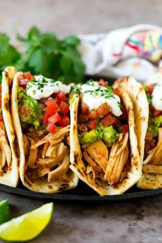 These slow cooker chicken tacos are filled with zesty pulled chicken, guacamole, pico de gallo and sour cream. The chicken only requires 4 ingredients and can be in the crock pot with just 5 minutes. Pulled Chicken Tacos, Pulled Chicken Recipes, Yummy Chicken Recipes, Mexican Food Recipes, Pork Tacos, Shrimp Tacos, Recipes Dinner, Shredded Chicken, Crock Pot Chicken