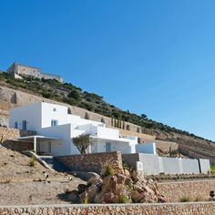 Rocks excavated from the site of this apartment building on the Greek island of Santorini were reused to form terraces so it blends with the mountains