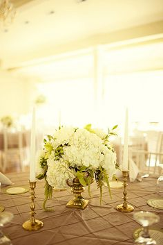 Short ivory and gold centerpiece with candlesticks.