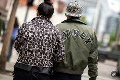 Couple on a street style photo taken during London Graduate Fashion Week 2014. Men wearing Avirex bomber jacket.