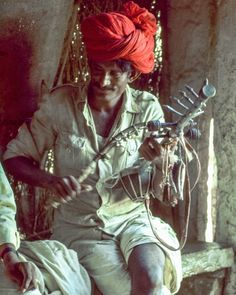 A wandering minstrel in Rajasthan India plays on a homemade 11-stringed instrument called a Ravanahatha sporting bells on his bow. He plays and sings for tips. Photo from my book #VanishingAsia #Rajasthan