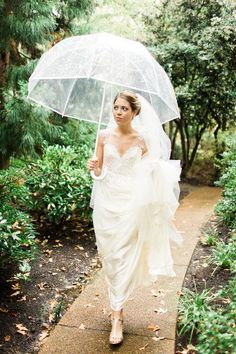 Rainy day wedding photo idea - bride poses with clear umbrella {b. flint photography}
