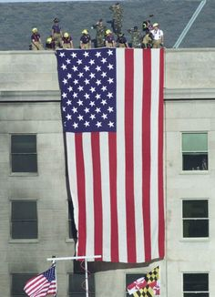Firefighters unfurl an American flag from the roof of the Pentagon Wednesday…