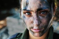 This young 18 year old woman, and IDF soldier, pauses after training in full equipment and war paint.