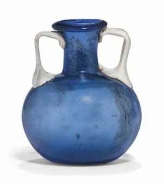 A ROMAN BLUE GLASS AMPHORISKOS - CIRCA 1ST CENTURY A.D. - Free-blown, with a globular body, cylindrical neck and flaring everted rim, with applied opaque white handles 2 ¾ in. (7 cm.) high
