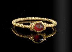 A gold ring with a gemstone garnet, Roman, 3rd century A.D.