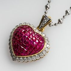 Invisible Set Ruby Diamond Heart Pendant Necklace 18K Two-Tone Gold, This gorgeous ruby heart pendant necklace is set with rectangular calibre cut rubies. Surrounding the rubies is a halo of bezel set diamond accents. The pendant hangs an a 16 inch modified ball chain and is crafted of solid 18k two-tone white and yellow gold. This pendant necklace is in very good condition and well designed.